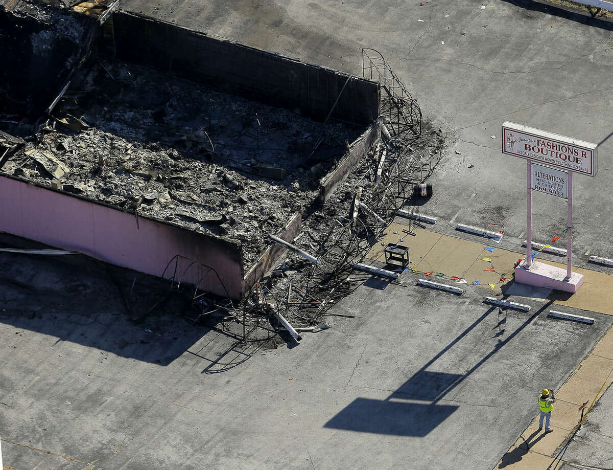 In this aerial photo, a worker surveys the scene at a charred building Tuesday, Nov. 25, 2014, in Ferguson, Mo., after it was burned in overnight protests following a grand jury's decision not to indict a white police officer in the killing of unarmed black 18-year-old Michael Brown. Monday night's protests were far more destructive than any of those that followed Brown's Aug. 9 death, with more than a dozen businesses badly damaged or destroyed. (AP Photo/Charlie Riedel)