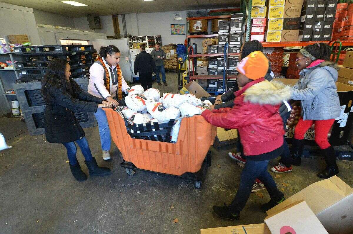Members of the Stamford Police Association Girls Leadership Program roll the bin of their donated turkeys to the freezer at The Food Bank of Lower Fairfield County