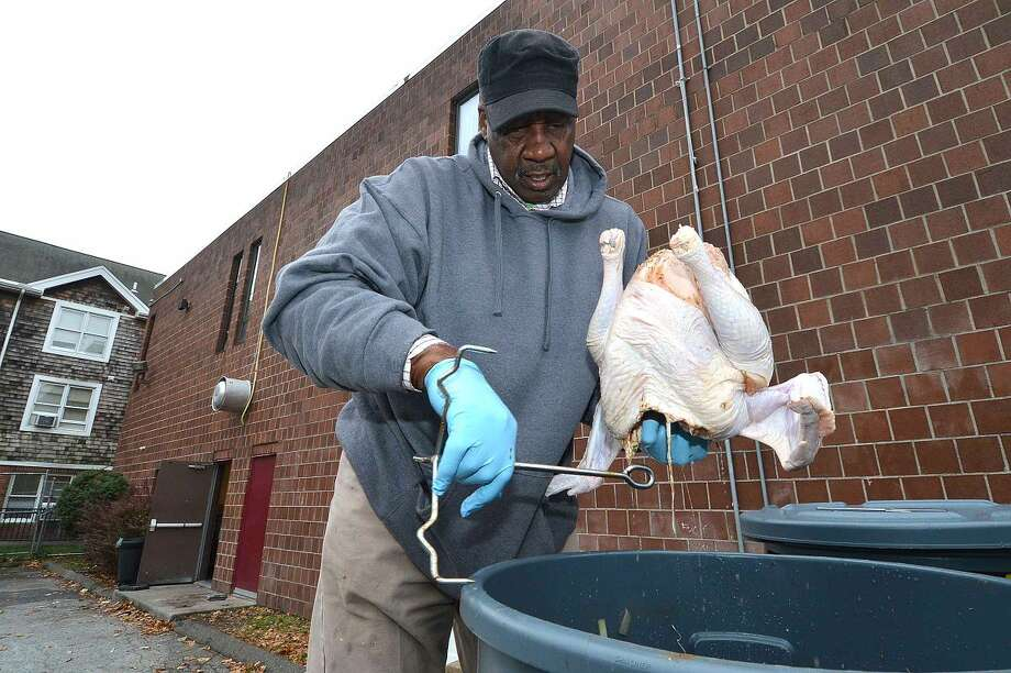 Hour Photo/Alex von Kleydorff Ernie Dumas pulls one of about 35 turkeys from the marinade for the South Norwalk Community Organization Thanksgiving dinner