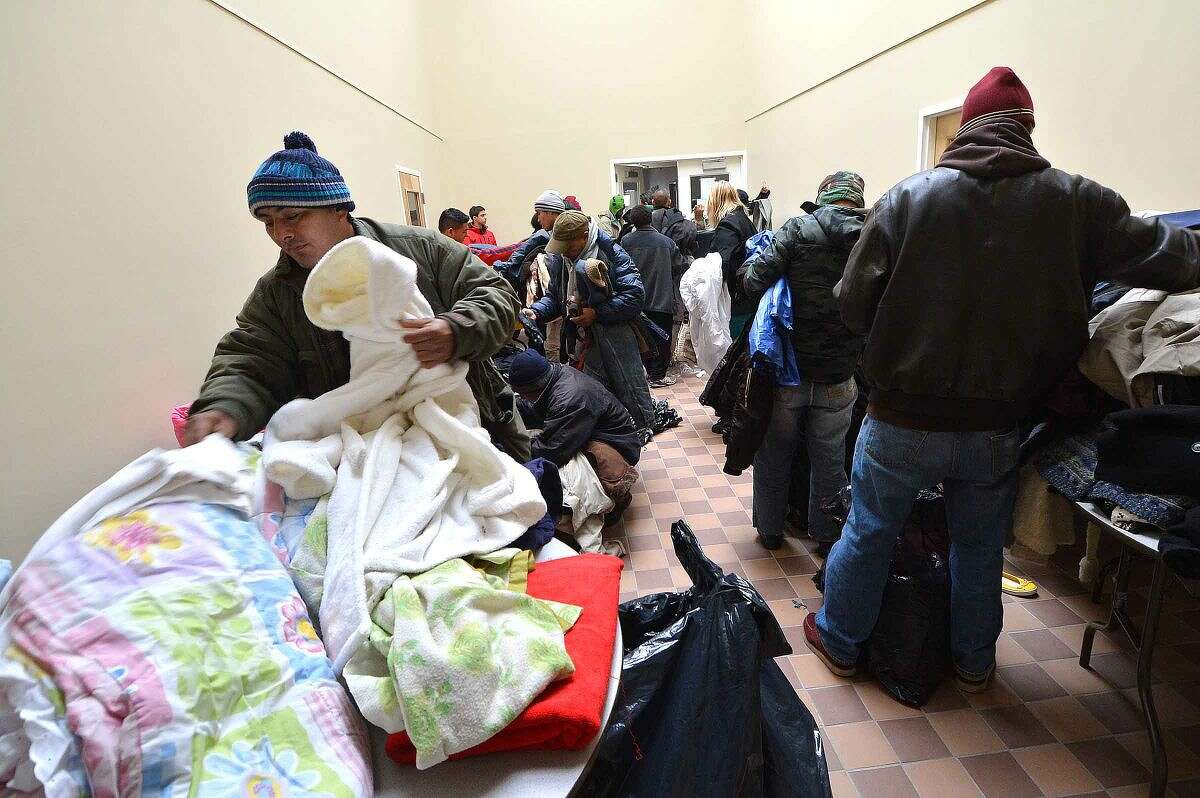 Hour Photo/Alex von Kleydorff Dontaed winter clothing gets picked up by those in need during South Norwalk Community Organization Thanksgiving dinner and coat giveaway