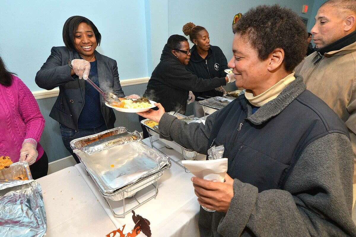 Hour Photo/Alex von Kleydorff Councilwoman Faye Bowman serves the sweet potatoes during South Norwalk Community Organization Thanksgiving dinner and coat giveaway on Thursday