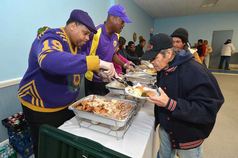 Hour Photo/Alex von Kleydorff Omega Psi Phi Fraternity members Greg Burnett and Eddie Artis help to serve at South Norwalk Community Organization Thanksgiving dinner and coat giveaway on Thursday