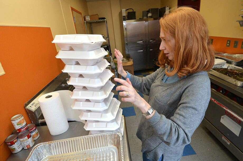 Hour Photo/Alex von Kleydorff Volunteer Tami Strauss counts to go meals in the kitchen during South Norwalk Community Organization Thanksgiving dinner
