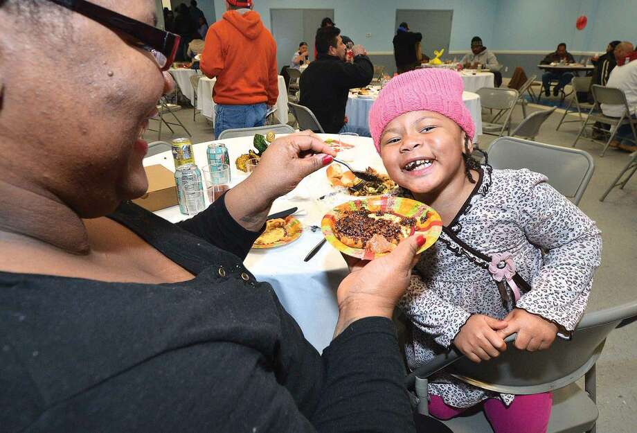 Hour Photo/Alex von Kleydorff South Norwalk Community Organization held its Thanksgiving dinner and coat giveaway on Thursday and Skyy Bryant gets a treat of some pecan pie from mom Chrystal after a Thanksgiving Dinner