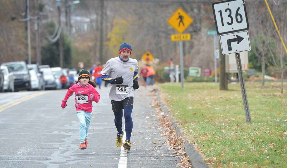 Hour Photo/Alex von Kleydorff Father and Daughter team of Radek and 8yr old Kalina Zapert head to the finish line first in their class at Rowayton Turkey Trot