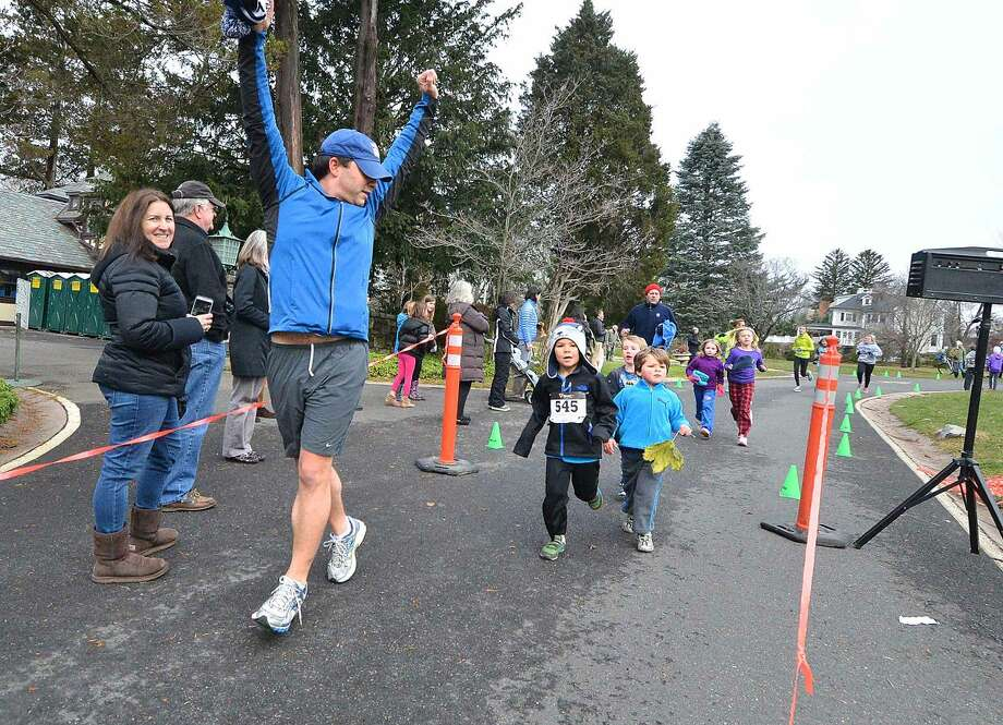 Hour Photo/Alex von Kleydorff James Knowles crosses the finish line and encourages his sons Oscar and James with him during the Rowayton Turkey Trot