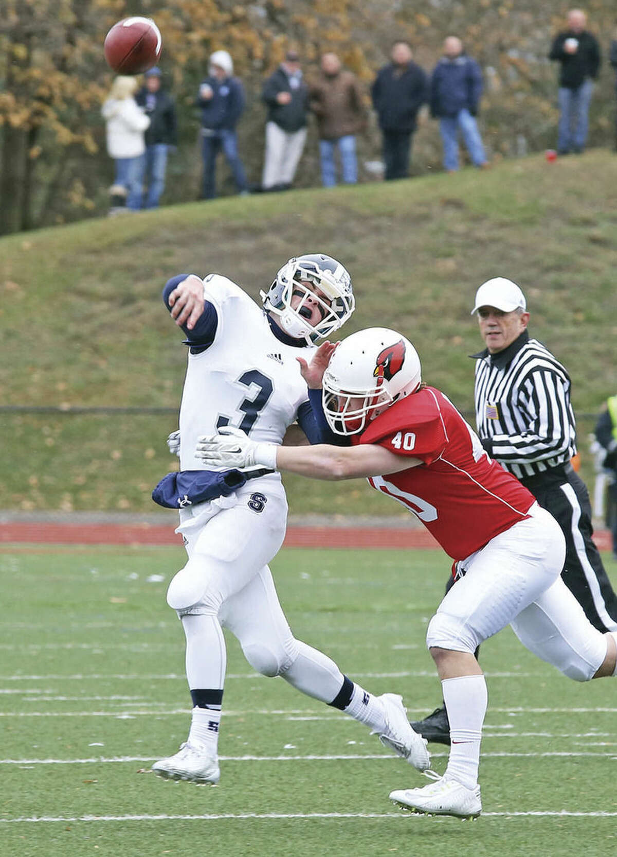 Hour photo/Danielle Calloway Staples quarterback Teddy Coogan, left, gets off a pass during the Thanksgiving game against Greenwich Thursday morning.
