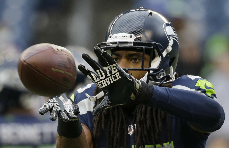 "FILE - In this Nov. 9, 2014, file photo, Seattle Seahawks cornerback Richard Sherman warms ups before an NFL football game against the New York Giants in Seattle. For the first time since flexible scheduling came to ""Sunday Night Football"" in 2006, the NFL could go an entire season without needing it. Seahawks-Cardinals in Week 16 keeps getting juicer with Arizona's improbable run to the league's best record and the defending Super Bowl champs' wobbly playoff hopes. (AP Photo/Elaine Thompson, File)"
