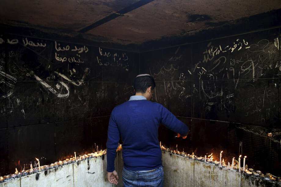 In this Thursday, Nov. 20, 2014 photo, an Iranian Jewish man lights candles at the at the tomb of Harav Oursharga, one of the holiest Jewish sites in Iran, in the city of Yazd 420 miles (676 kilometers) south of capital Tehran. More than a thousand people trekked across Iran this past week to visit a shrine in this ancient Persian city, a pilgrimages like many others in the Islamic Republic until you notice men there wearing yarmulkes. (AP Photo/Ebrahim Noroozi)