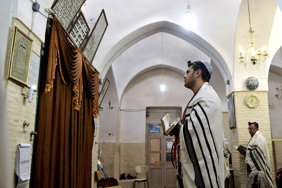 In this Friday, Nov. 21, 2014 photo, an Iranian Jewish man prays at the Molla Agha Baba Synagogue, in the city of Yazd 420 miles (676 kilometers) south of capital Tehran, Iran. More than a thousand people trekked across Iran this past week to visit a shrine in this ancient Persian city, a pilgrimages like many others in the Islamic Republic until you notice men there wearing yarmulkes. (AP Photo/Ebrahim Noroozi)