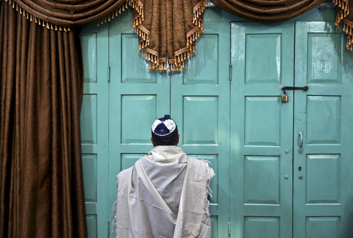 In this Thursday, Nov. 20, 2014 photo, an Iranian Jewish man prays at the Molla Agha Baba Synagogue, in the city of Yazd 420 miles (676 kilometers) south of capital Tehran, Iran. More than a thousand people trekked across Iran this past week to visit a shrine in this ancient Persian city, a pilgrimages like many others in the Islamic Republic until you notice men there wearing yarmulkes. (AP Photo/Ebrahim Noroozi)