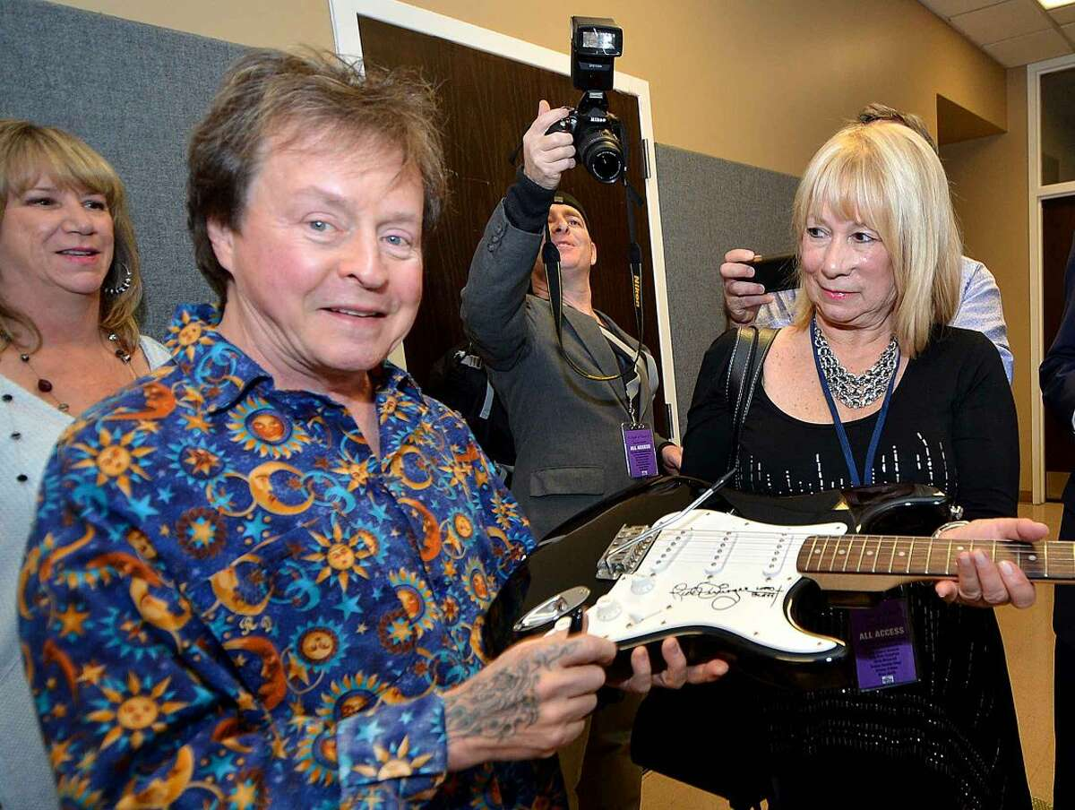 Hour Photo/Alex von Kleydorff Musician Rick Derringer signs a guitar to be auctioned for Charlene Lebo, one of the organizers for the 5th annual 'Night of Music' at Fairfield University's Quick Center for The Performing Arts Saturday night to benefit the Lebo-DeSantie Center for Liver and Pancreatic Disease at St. Vincent Hospital