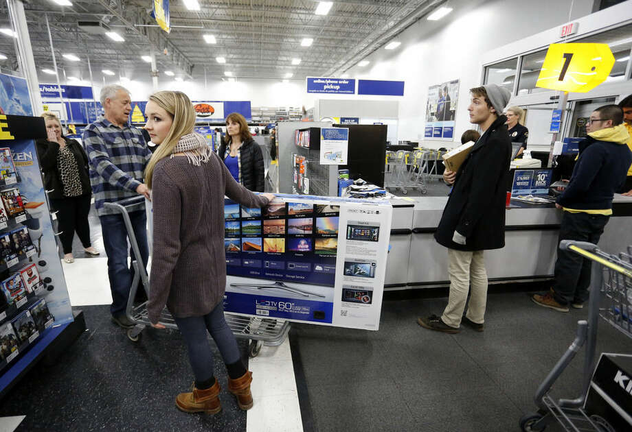 Shoppers purchase items during a Thanksgiving day sale at a Best Buy store in Broomfield, Colo., on Thursday, Nov. 27, 2014. (AP Photo/Brennan Linsley)