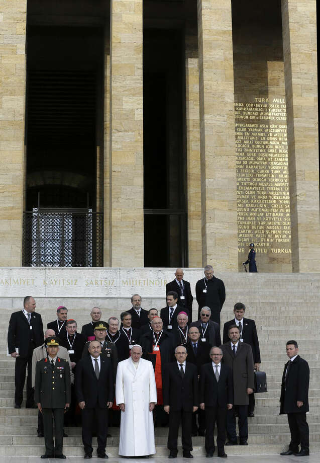 Pope Francis poses for the photographers with officials, at the mausoleum of the Turkish republic's founder, Mustafa Kemal Ataturk, in Ankara on Friday, Nov. 28, 2014. Pope Francis arrived in Turkey on Friday at a sensitive moment for the Muslim nation, as it cares for 1.6 million refugees and weighs how to deal with the Islamic State group as its fighters grab chunks of Syria and Iraq across Turkey's southern border. (AP Photo/Thanassis Stavrakis)