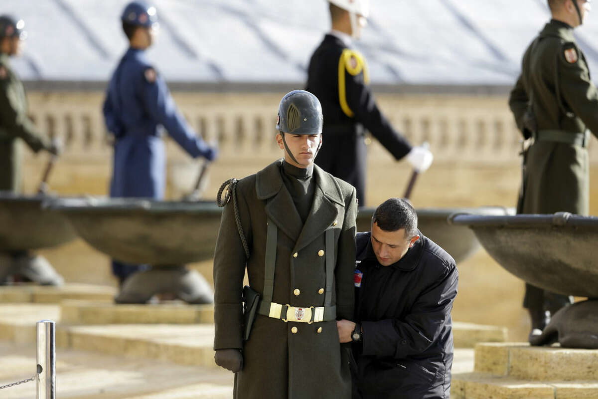 A man of the staff adjusts the uniform of a guard shortly before Pope Francis' visit at the mausoleum of the Turkish republic's founder, Mustafa Kemal Ataturk, in Ankara, Friday, Nov. 28, 2014. Pope Francis arrived in Turkey on Friday at a sensitive moment for the Muslim nation, as it cares for 1.6 million refugees and weighs how to deal with the Islamic State group as its fighters grab chunks of Syria and Iraq across Turkey's southern border. (AP Photo/Thanassis Stavrakis)