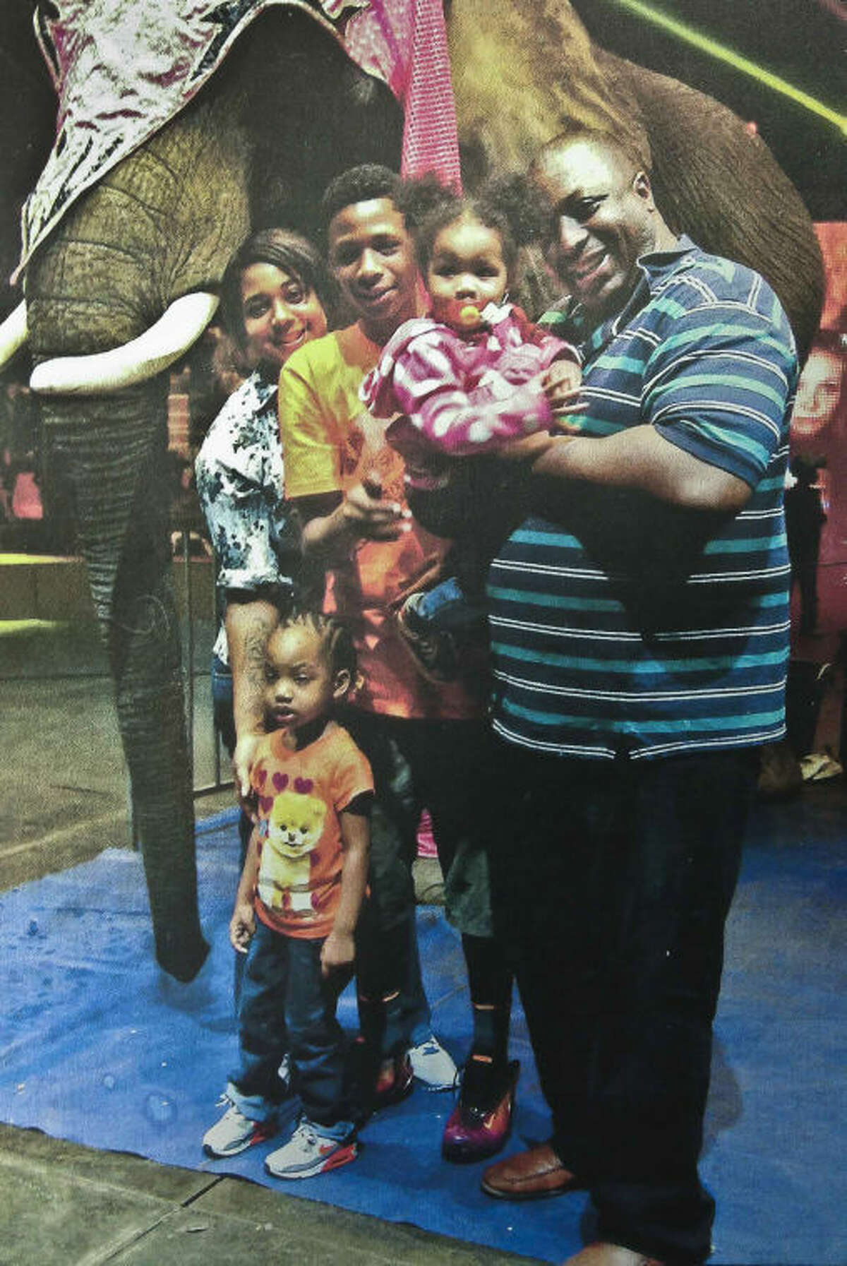 FILE- In this undated family file photo provided by the National Action Network, Saturday, July 19, 2014, Eric Garner, right, poses with his children during a family outing. On Friday, Aug. 1, 2014, the New York City medical examiner announced that the chokehold used on Garner by a white police officer caused his death. The death was ruled a homicide. (AP Photo/Family photo via National Action Network, File)