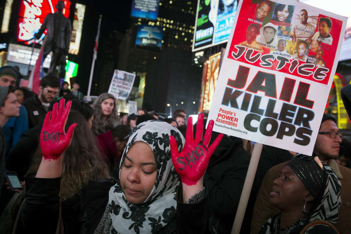 FILE- In this Nov. 25, 2014 file photo, demonstrator Maryam Said raises her painted hands during a protest against a grand jury's decision on Monday not to indict Ferguson police officer Darren Wilson in the shooting of Michael Brown in New York. After Brown's death at the hands of a white police officer his legacy continues to evolve. (AP Photo/John Minchillo, File)