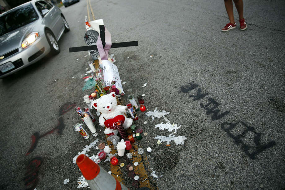 FILE - In this Aug. 11, 2014, file photo, a makeshift memorial sits in the middle of the street where 18-year-old Michael Brown was shot and killed in Ferguson, Mo. After Brown's Aug. 9 shooting death at the hands of a white police officer his legacy continues to evolve. (AP Photo/Jeff Roberson, File)