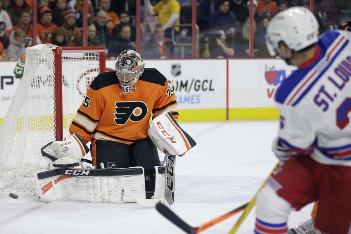 Philadelphia Flyers' Steve Mason, left, blocks a shot by New York Rangers' Martin St. Louis during the first period of an NHL hockey game, Friday, Nov. 28, 2014, in Philadelphia. (AP Photo/Matt Slocum)