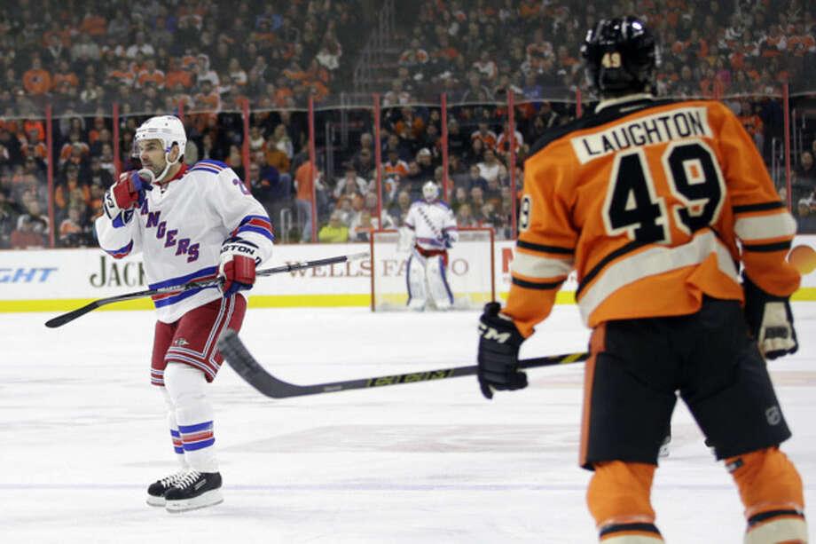 New York Rangers' Dan Boyle, left, celebrates past Philadelphia Flyers' Scott Laughton after Boyle's goal during the first period of an NHL hockey game, Friday, Nov. 28, 2014, in Philadelphia. (AP Photo/Matt Slocum)