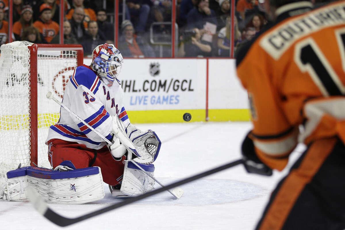 New York Rangers' Cam Talbot, left, blocks a shot by Philadelphia Flyers' Sean Couturier (14) during the second period of an NHL hockey game, Friday, Nov. 28, 2014, in Philadelphia. (AP Photo/Matt Slocum)