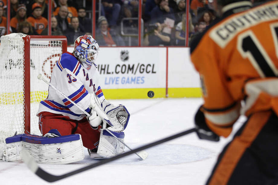 New York Rangers' Cam Talbot, left, blocks a shot by Philadelphia Flyers' Sean Couturier (14) during the second period of an NHL hockey game, Friday, Nov. 28, 2014, in Philadelphia. (AP Photo/Matt Slocum)