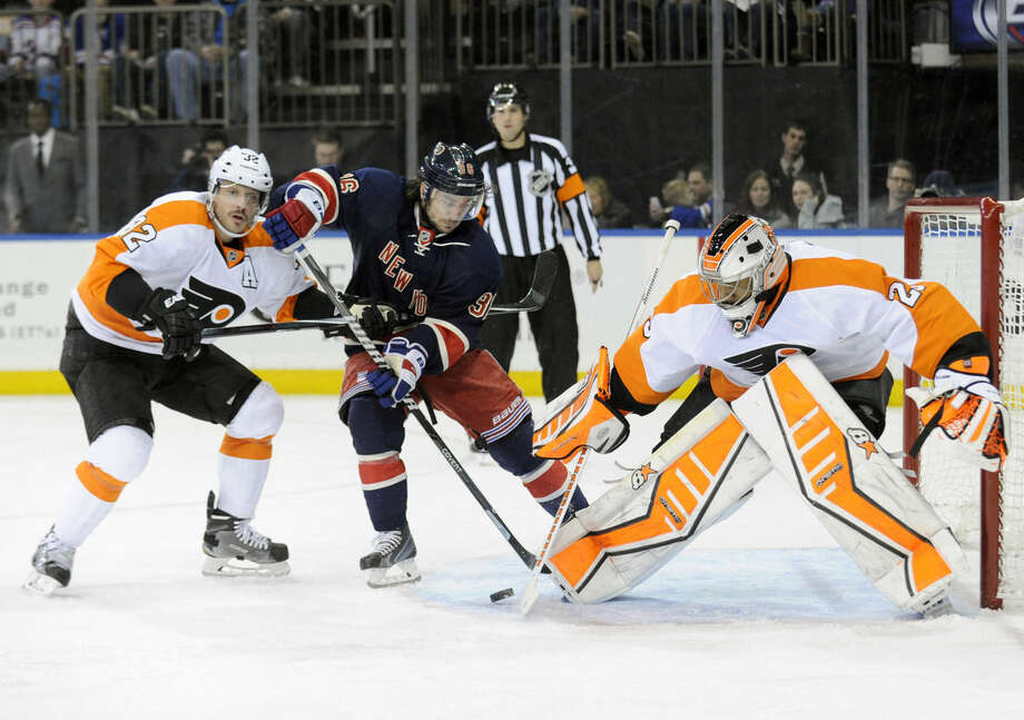 Philadelphia Flyers goaltender Ray Emery, right, deflects the puck as New York Rangers' Mats Zuccarello is checked by Flyers' Mark Streit during the second period of an NHL hockey game Saturday, Nov. 29, 2014, at Madison Square Garden in New York. (AP Photo/Bill Kostroun)