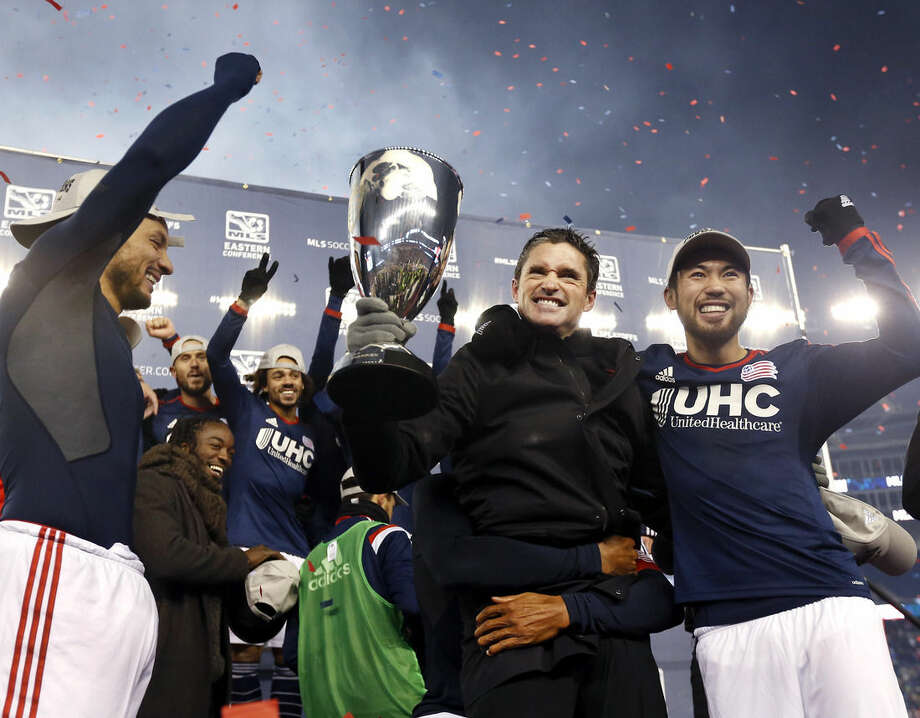 New England Revolution head coach Jay Heaps holds the MLS Eastern Conference Champion's Cup as he, Jermaine Jones, far left, Lee Nguyen, far right, and teammates celebrate after the second soccer game against the New York Red Bulls of the MLS Eastern Conference final in Foxborough, Mass., Saturday, Nov. 29, 2014. The match ended 2-2 and New England advanced to the MLS Cup with a two-game aggregate 4-3. (AP Photo/Elise Amendola)