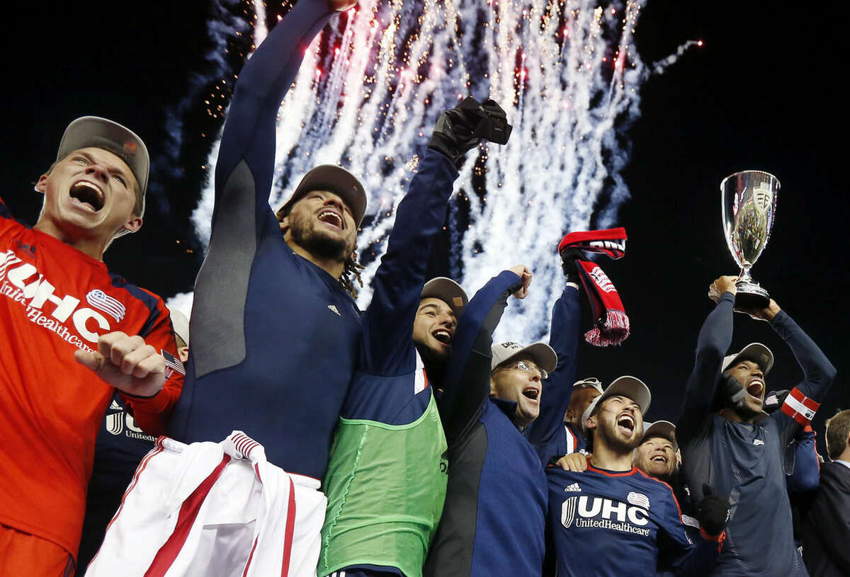 New England Revolution's Jose Goncalves, far right, holds the MLS Eastern Conference Champion's Cup aloft as he and goalkeeper Bobby Shuttleworth, far left, and Jermaine Jones, second from left, and others celebrate after the second soccer game against the New York Red Bulls of the MLS Eastern Conference final in Foxborough, Mass., Saturday, Nov. 29, 2014. The match ended 2-2 and New England advanced to the MLS Cup with a two-game aggregate 4-3. (AP Photo/Elise Amendola)