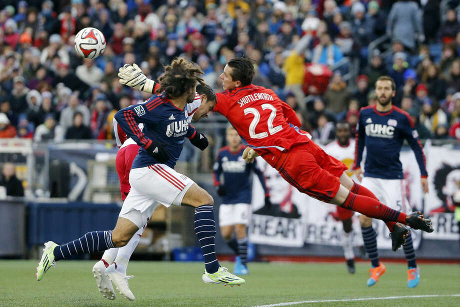 New England Revolution goalkeeper Bobby Shuttleworth (22) makes a save on a bid by New York Red Bulls midfielder Tim Cahill (partially hidden) as Revolution's Kevin Alston, foreground, defends during the first half of the second soccer game of the MLS Eastern Conference final in Foxborough, Mass., Saturday, Nov. 29, 2014. (AP Photo/Elise Amendola)