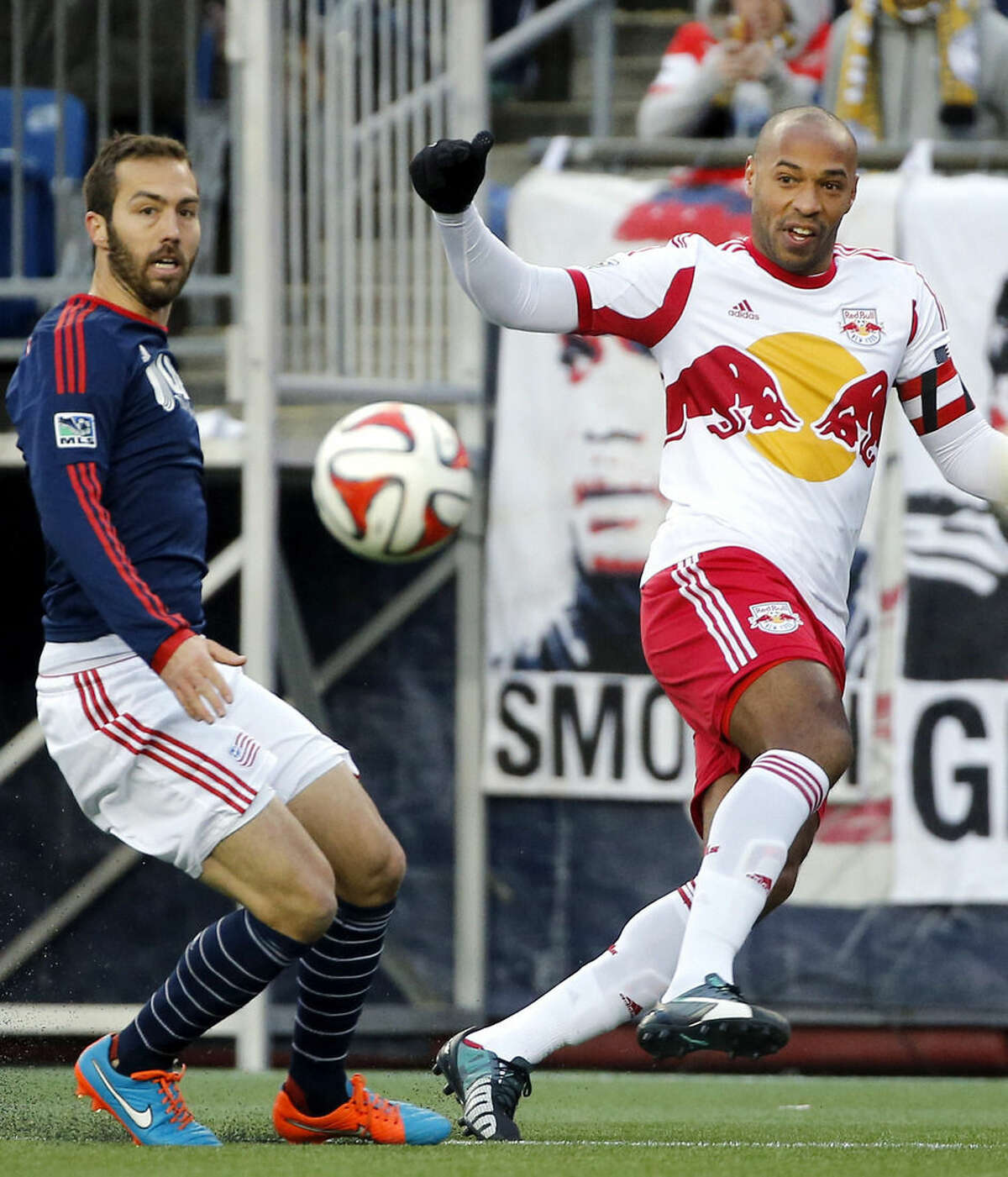 New York Red Bulls forward Thierry Henry, right, sends the ball toward the goal as New England Revolution's A.J. Soares defends, left, during the first half of the second soccer game of the MLS Eastern Conference final in Foxborough, Mass., Saturday, Nov. 29, 2014. The match ended 2-2 and New England advanced to the MLS Cup with a two-game aggregate 4-3. (AP Photo/Elise Amendola)