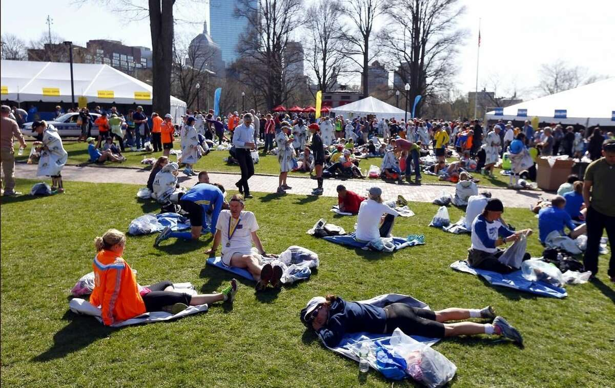 FILE - In this April 21, 2014 file photo, runners rest at Boston Common after completing in the118th Boston Marathon in Boston. The city is bidding on the 2024 Summer Olympics, and the Common could be used as a venue for beach volleyball. The crux of the proposal is a walkable, sustainable, technology-based event that would harness the resources of the area's 100 colleges and universities to keep the Games affordable and compact. (AP Photo/Matt Rourke, File)