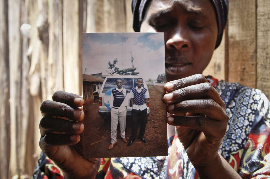 In this May 9, 2014 photo, Saida Mohammed Kaburu displays a photograph of her son Mohamed Kaburu, as she speaks to The Associated Press in Nyeri, Kenya. Mohamed Kaburu's body and those of four of his friends were discovered April 17 with bullet holes in their heads deep in a forest near the central Kenyan town of Nyeri. The last time the five were seen was in police custody according to their families. (AP Photo/Khalil Senosi)
