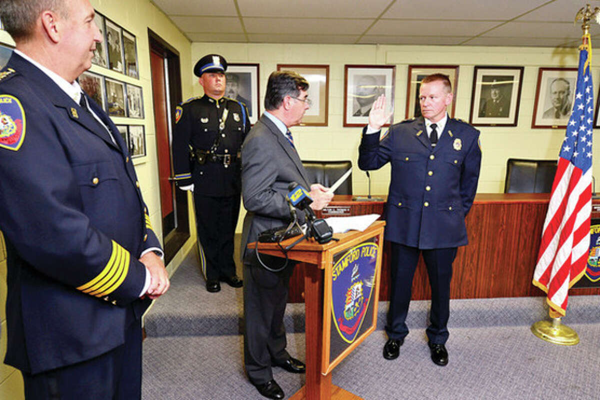 Hour photo / Erik Trautmann Stamford Police Department's new Assistant Chief Timothy Shaw is sworn in by Mayor Michael Pavia as Chief Jon Fontineau looks on Wednesday at police headquarters.