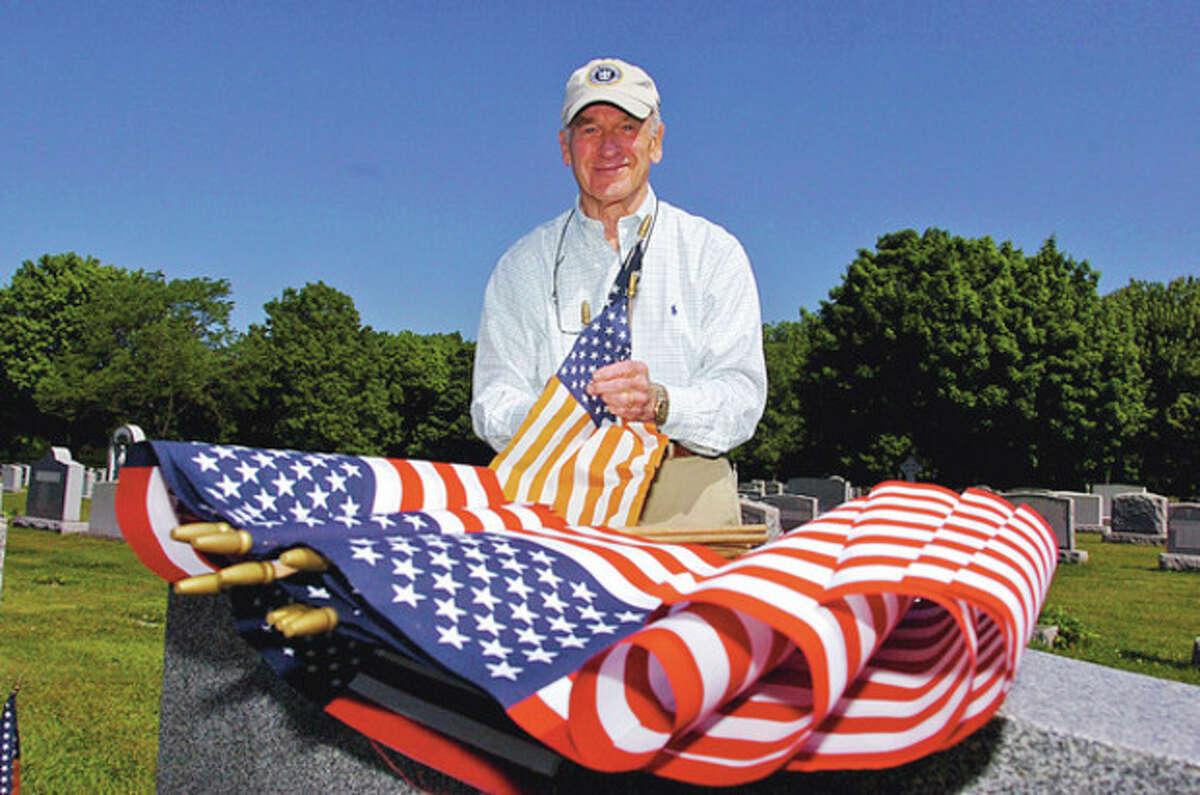 Hugh Johannessen replaces an old flag during the Northrop Grumman sponsored flag-placing ceremony for veterans' graves at St. John's Cemetery in Norwalk Saturday. Hour photo / Erik Trautmann