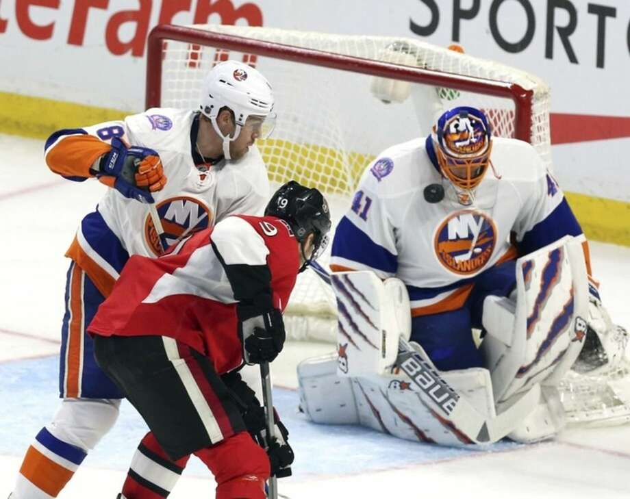 New York Islanders goaltender Jaroslav Halak (41) blocks the puck with his face mask as teammate Griffin Rienhart (8)and Ottawa Senators' Milan Michalek (9) look on during second-period NHL hockey game action in Ottawa, Ontario, Thursday, Dec. 4, 2014. (AP Photo/The Canadian Press, Fred Chartrand)