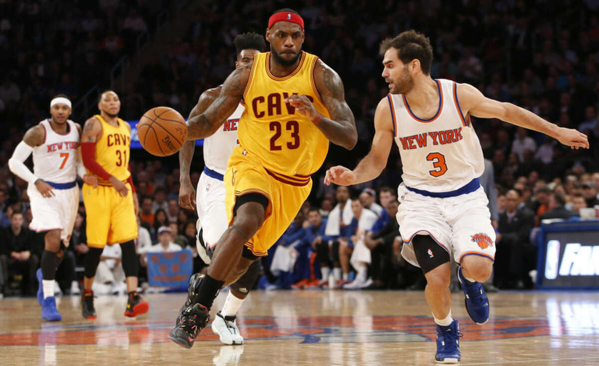 New York Knicks forward Carmelo Anthony (7) watches, far left, as Cleveland Cavaliers forward LeBron James (23) drives toward the basket beside New York Knicks guard Jose Calderon (3) in the first half of an NBA basketball game at Madison Square Garden in New York, Thursday, Dec. 4, 2014. (AP Photo/Kathy Willens)