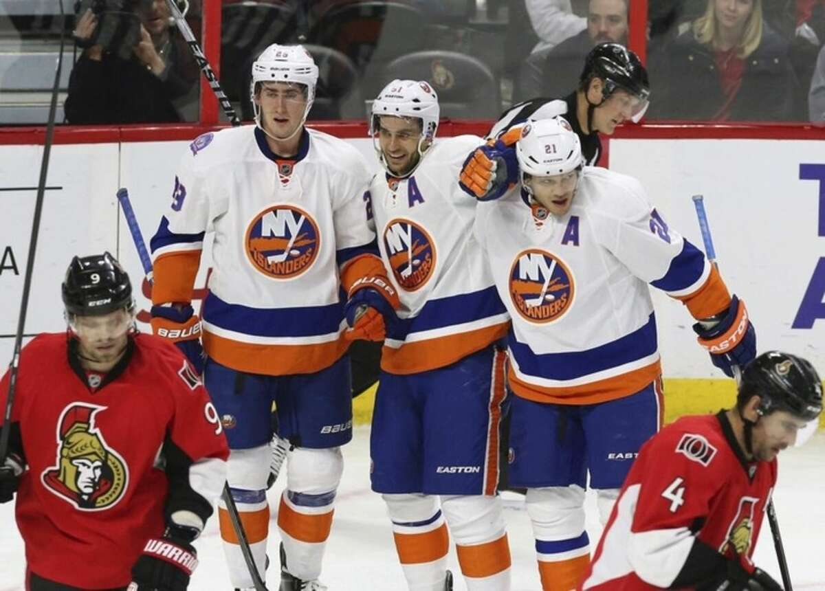 New York Islanders' Brock Nelson (29) Frans Nielsen (51) and Kyle Okposo (21) celebrate Nelson's goal during second-period NHL hockey game action against the Ottawa Senators in Ottawa, Ontario, Thursday, Dec. 4, 2014. (AP Photo/The Canadian Press, Fred Chartrand)