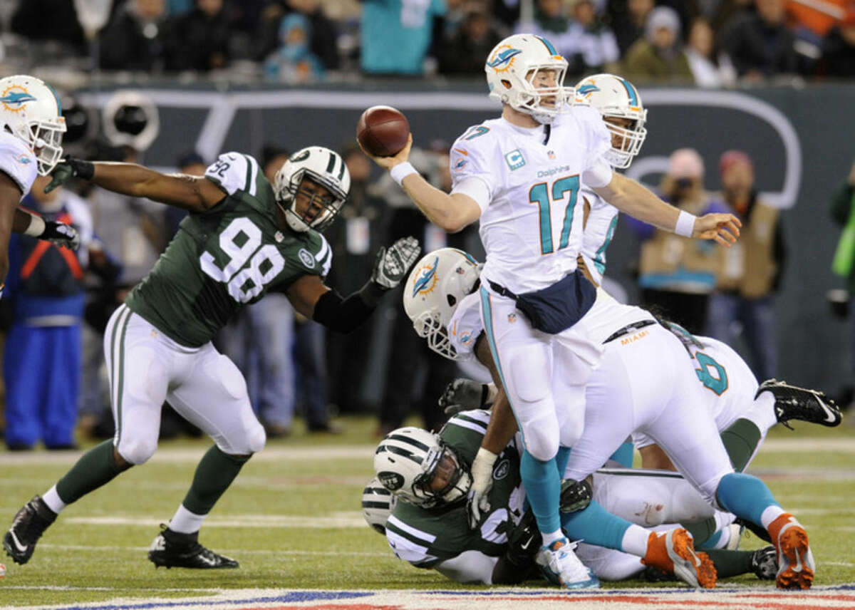 Miami Dolphins quarterback Ryan Tannehill (17) throws a pass under pressure from the New York Jets during the third quarter of an NFL football game, Monday, Dec. 1, 2014, in East Rutherford, N.J. Miami Dolphins running back Lamar Miller (26) tipped the pass on the play resulting in an interception for the Jets. (AP Photo/Bill Kostroun)