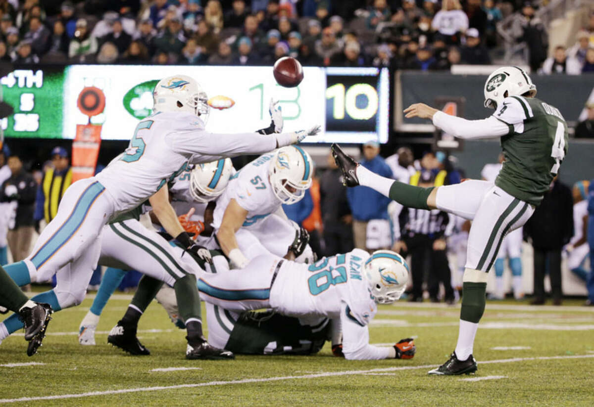 Miami Dolphins defensive end Dion Jordan (95) blocks a punt by New York Jets punter Ryan Quigley (4) during the third quarter of an NFL football game, Monday, Dec. 1, 2014, in East Rutherford, N.J. (AP Photo/Julio Cortez)