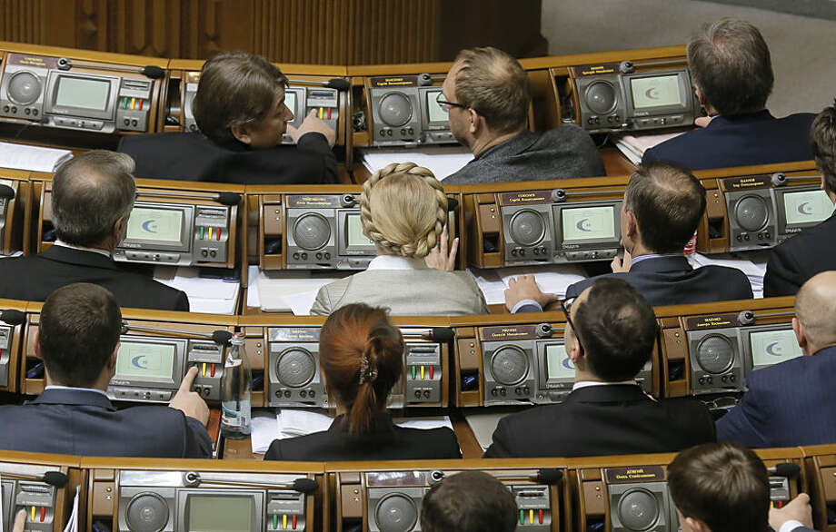 Former Prime Minister and leader of the Fatherland party Yulia Tymoshenko, center, and lawmakers from her party vote during a parliament session in Kiev, Ukraine, Tuesday, Dec. 2, 2014. Ukraine's parliament has approved the formation of a new government, bringing an end to weeks of behind-the-scenes political wrangling following an October election that ushered in a group of ardently pro-Western parties. (AP Photo/Efrem Lukatsky)