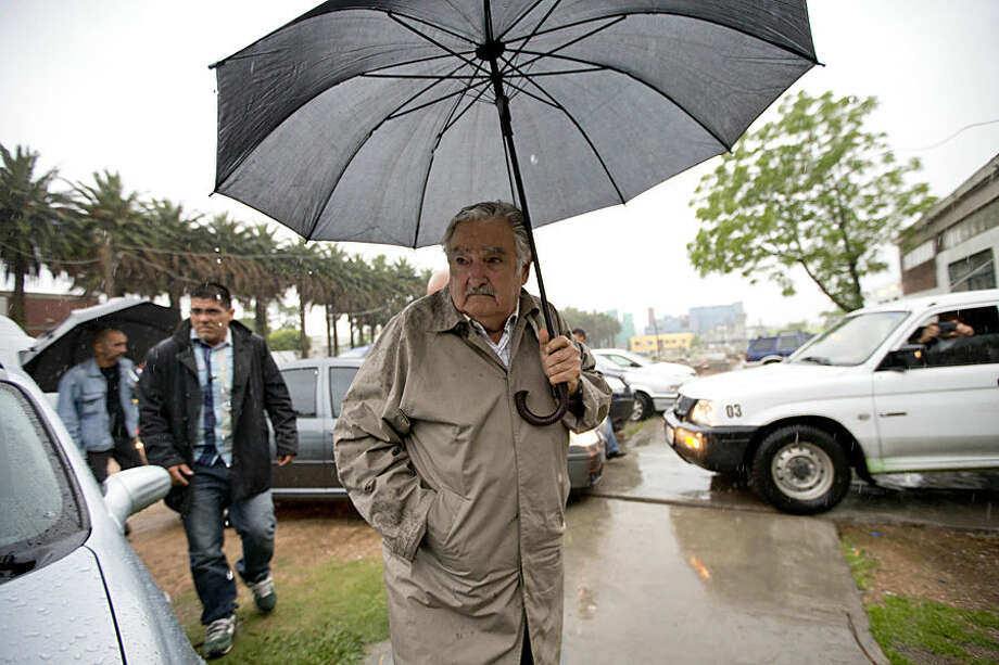 Uruguay's president, Jose Mujica, center, arrives to cast his vote in the presidential runoff election, Sunday, Nov. 30, 2014, in Montevideo, Uruguay. Broad Front coalition candidate and former president Tabare Vazquez is favored to win the runoff on the back of a strong economy. (AP Photo/Natacha Pisarenko)