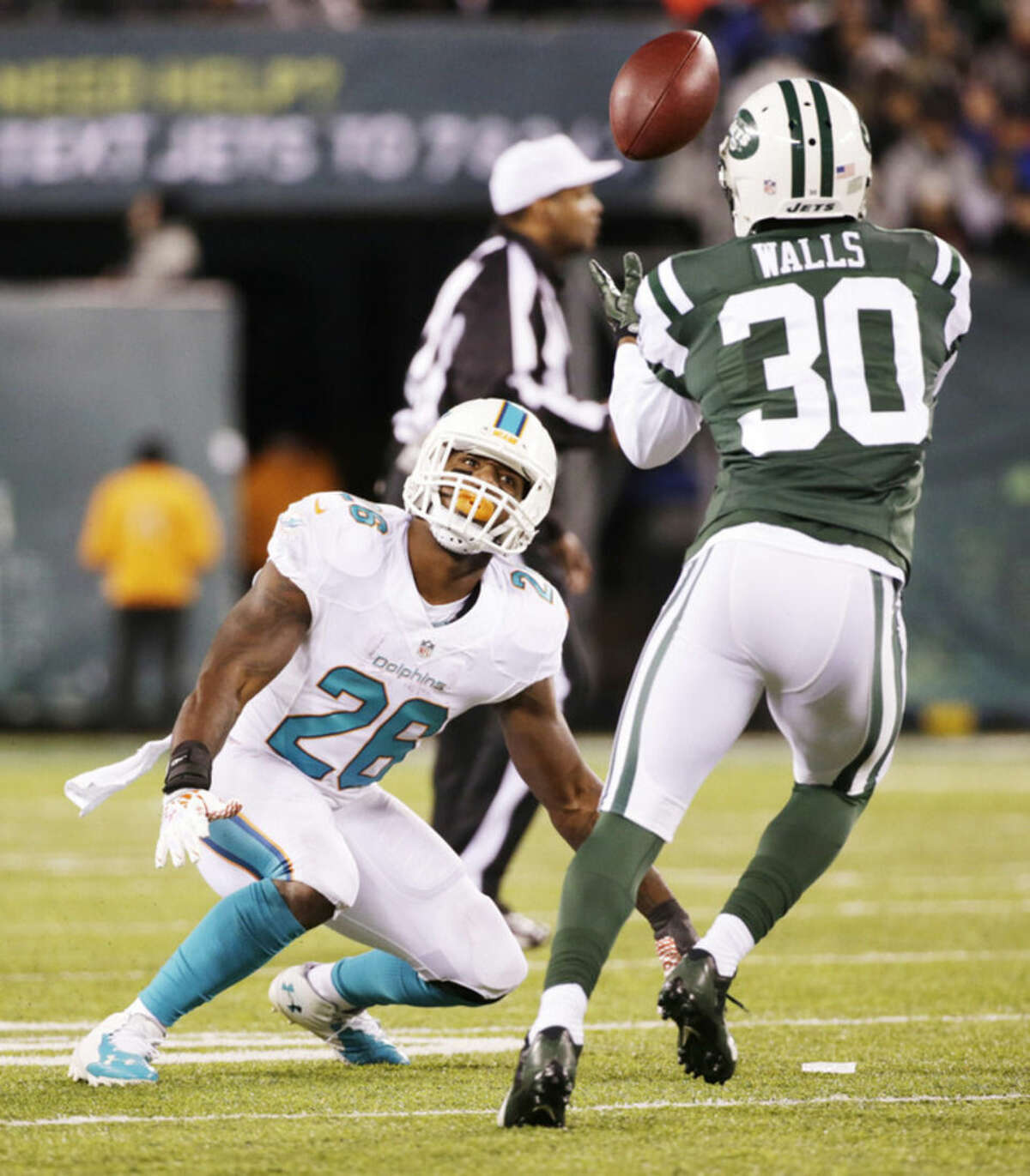 Miami Dolphins running back Lamar Miller (26) watches as New York Jets cornerback Darrin Walls (30) intercepts the ball after Miller tipped a pass during the third quarter of an NFL football game, Monday, Dec. 1, 2014, in East Rutherford, N.J. (AP Photo/Julio Cortez)