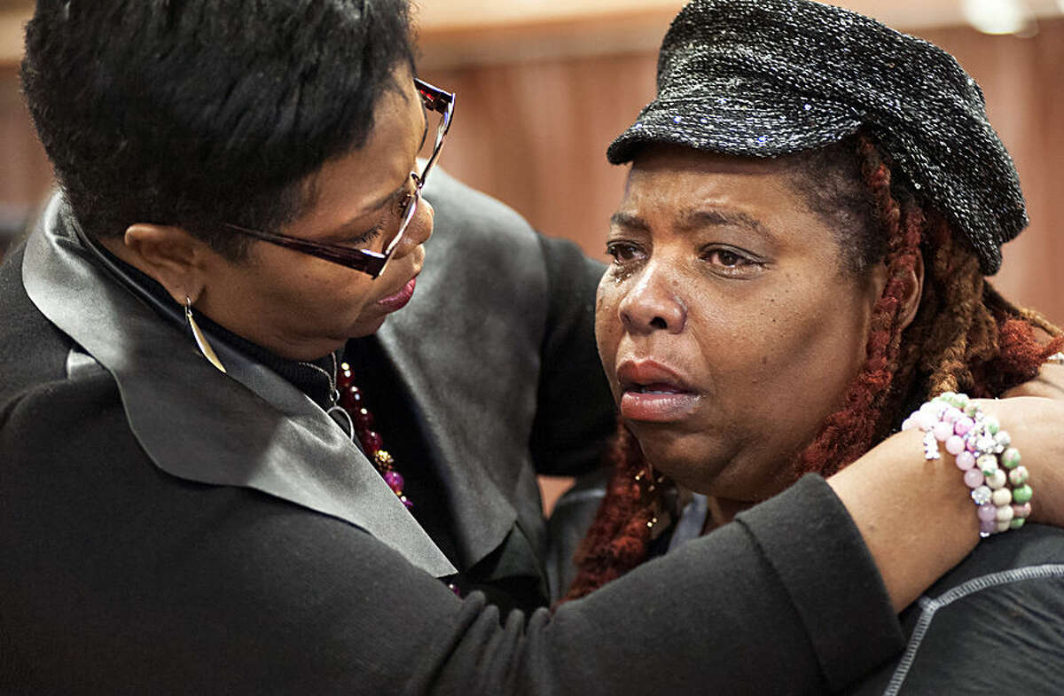 Dell Taylor, right, is comforted by the Rev.Traci Blackmon, a member of the Ferguson Commission appointed by Missouri Gov. Jay Nixon, during the opening meeting of the commission at the Ferguson Community Center in Ferguson, Mo. Monday, Dec. 1, 2014. The 16-person panel was chosen by Missouri's governor to help find long-term solutions after the Ferguson police shooting of an unarmed man. (AP Photo/Sid Hastings)