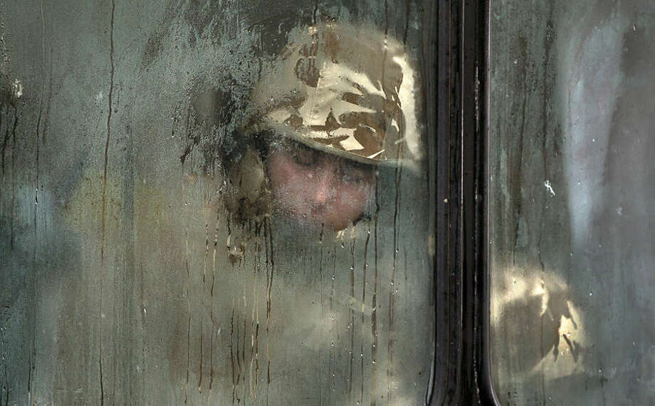 A Romanian soldier sleeps on a bus before taking part in a military parade to mark Romania's national day in Bucharest, Romania, Monday Dec. 1, 2014. Romanians braved the cold weather to watch the traditional armed forces parade, held outside the Palace of Parliament formerly the House of the People, built during the rule of communist dictator Nicolae Ceausescu.(AP Photo/Vadim Ghirda)