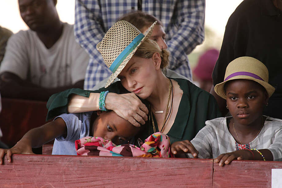 U.S singer Madonna hugs her son David, left, while her daughter Mercy looks on in Kasungu, about 150 kilometers north of the capital Lilongwe, Sunday, Nov. 30, 2014. Madonna is currently visiting Malawi with her son David and daughter Mercy, where she has been working since 2006 with her non profit organization, Raising Malawi. (AP Photo/Tsvangirayi Mukwazhi)
