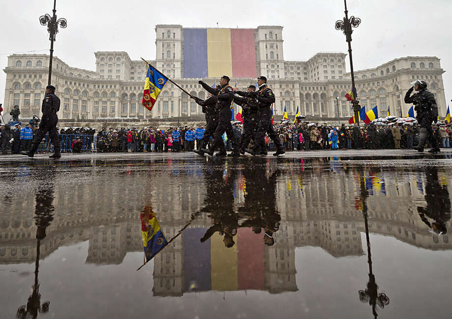 Romanian soldiers march during a military parade to mark Romania's national day in Bucharest, Romania, Monday, Dec. 1, 2014. Romanians braved the cold weather to watch the traditional armed forces parade, held outside the Palace of Parliament formerly the House of the People, seen in the background, built during the rule of communist dictator Nicolae Ceausescu. (AP Photo/Vadim Ghirda)
