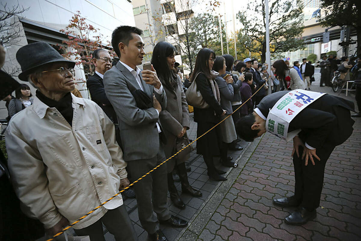 Kiyoto Tsuji, right, the ruling Liberal Democratic Party (LDP) candidate for a Tokyo district, bows to voters on a street as the campaigning for the lower house election officially begins Tuesday, Dec. 2, 2014 in Tokyo. Hundreds of candidates fanned out across Japan on Tuesday. Prime Minister Shinzo Abe of the LDP seeks public mandate for four more years. Abe dissolved the lower house of parliament on Nov. 20, forcing a snap poll on Dec. 14. (AP Photo/Eugene Hoshiko)