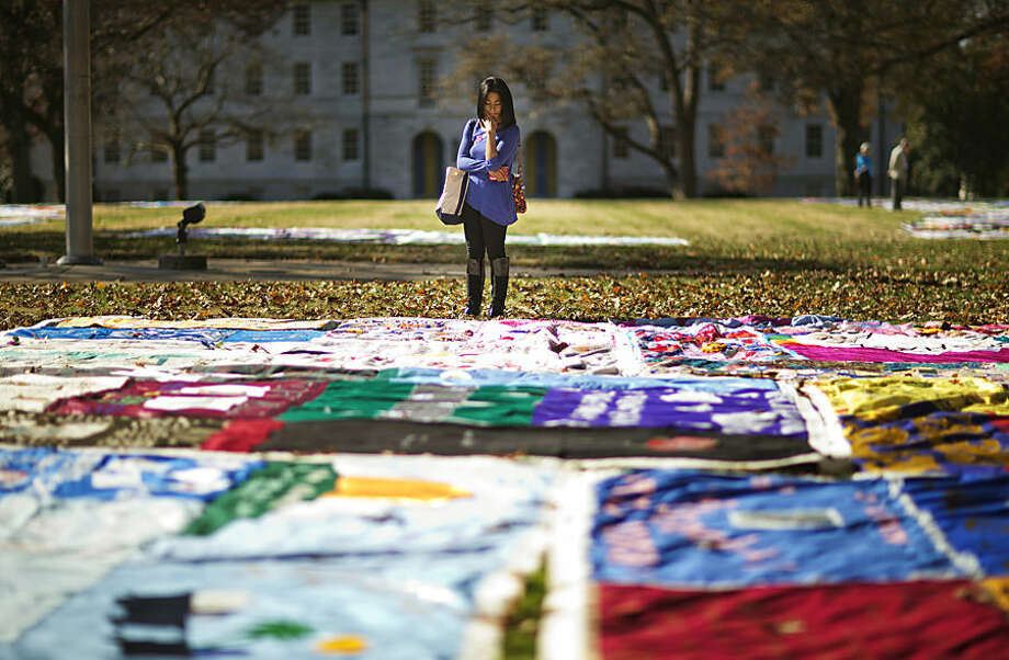 Student Christina Batipps browses over a display of AIDS memorial quilt panels on display as part of World AIDS Day at Emory University, Monday, Dec. 1, 2014, in Atlanta. World AIDS Day is marked on Dec. 1 every year to raise awareness about HIV/AIDS. (AP Photo/David Goldman)