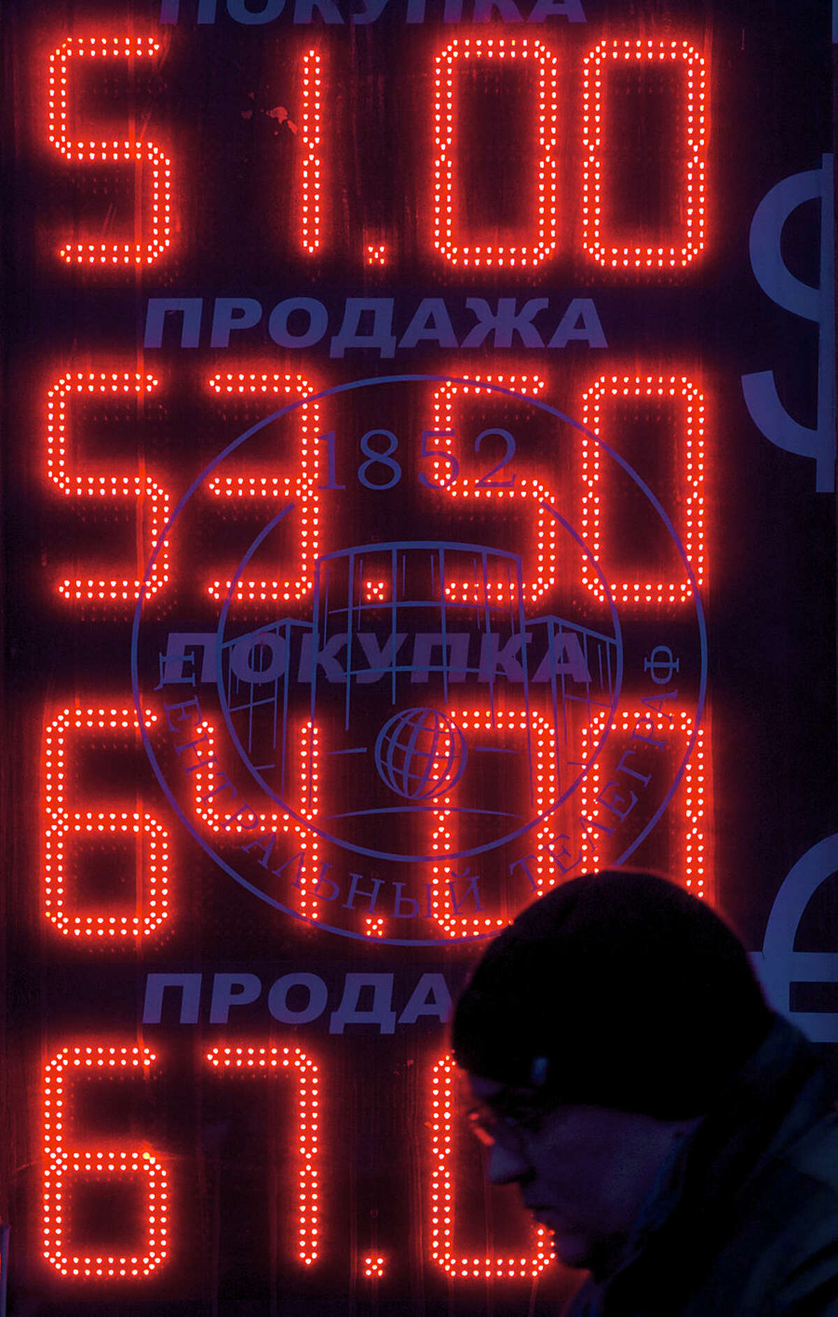 A man walks past a currency exchange booth in downtown Moscow, Russia, Tuesday, Dec. 2, 2014. The Russian government has for the first time acknowledged that the country will fall into recession next year, battered by the plunge in the price of its oil exports. The top two figures indicate the spread on the dollar-ruble rate and the bottom two figures indicate the the euro-ruble rate. (AP Photo/Ivan Sekretarev)